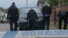 Police inspect the murder scene in Luton today.