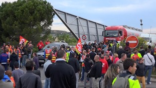 Workers blockade a road stopping an oil truck from getting past