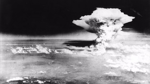 An atomic cloud billows following the explosion of the first atomic bomb in Hiroshima
