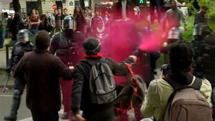 A protester sprays riot police with pink paint.