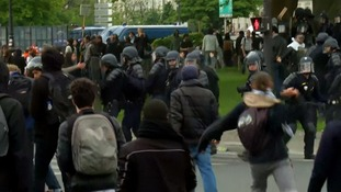 A protester throws a rock at a police line.
