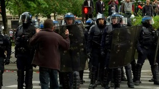 A protester confronts a line of riot police.