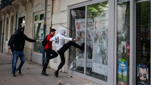 Youths kick the window of a bank in Nantes.