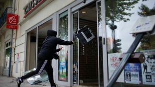 A youth throws a printer through the doors of a bank during the demonstration.