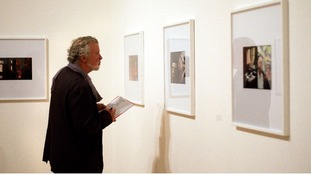 A member of the public looks at photos by Luke Fowler,