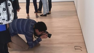 A visitor to the museum takes a picture of the 'exhibit'