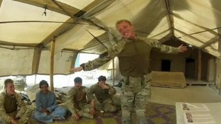 A British soldier dances to the beat of an Afghan drum