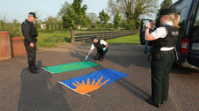 Police photograph flags as part of the operation in Lurgan.