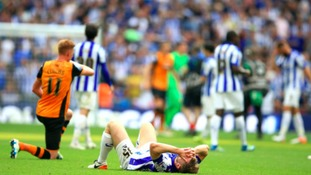 Sheffield Wednesday's Tom Lees lies dejected on the pitch after the final whistle