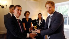 Prince Harry hands over the medal won by Elizabeth Marks to Dr Alain Vuylsteke.
