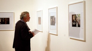 A member of the public looks at photos by Luke Fowler, who is shortlisted for the 2012 Turner prize, at Tate Britain in London.