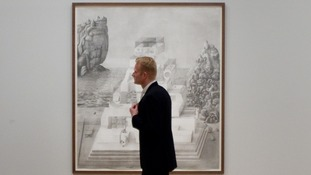 A member of the public walks past a large scale drawing by Paul Noble who is shortlisted for the 2012 Turner prize at Tate Britain.