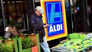 A customer walks out of an Aldi supermarket store in South Derbyshire.