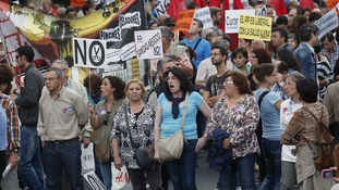 Demonstrators march with banners during a protest against public health and education cuts in Madrid.