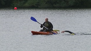 A soldier swimming next to a canoe.