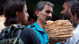 A man holds bread as a Syria rebel fighter stands guard