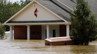 A casket is seen in front of a partially submerged church in Ascension Parish.