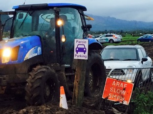 tractor towing car out of mud
