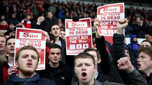 Liverpool fans hold up signs protesting against the Sun newspaper.