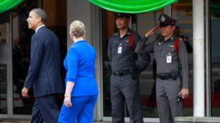 A Thai policeman salutes as President Obama and Hillary Clinton pass by