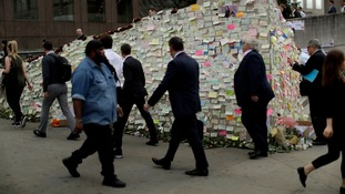 Commuters walk past messages of support