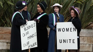 Students re-create a protest march by suffragettes.