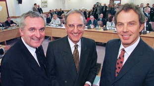 British Prime Minister Tony Blair (R) US Senator George Mitchell (C) and Irish Prime Minister Bertie Ahern smiling after they signed the historic agreement for peace in Northern Ireland.