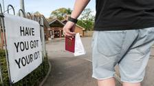 A voter carries his passport along with his poll card in Knaphill, Woking.