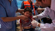Medics treat a Palestinian child suffering from teargas inhalation during a protest near the Gaza Strip.
