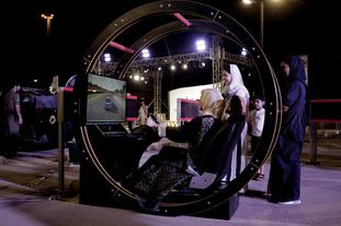 A woman tests a driving simulator at a road safety event for female drivers