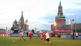 Fans from England and Russia take part in a football match in Red Square, Moscow.