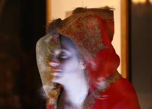 The face of a Royal Collection Trust employee reflected in the hood of Napoleon's cloak, part of the Prince & Patron exhibition, part of the summer opening of Buckingham Palace. (Yui Mok/PA)