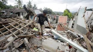A man walks through debris from Sunday's earthquake in West Lombok, Indonesia.