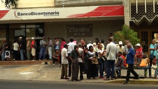 Residents wait in line to take out their drastically devalued money before it is too late.