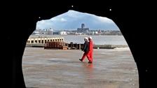 Two employees of Cammell Laird's ship builders in Birkenhead are seen through a hole in the yard's wall.