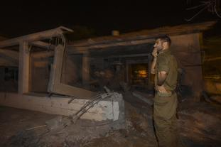 An Israeli soldier walks by a house damaged in Ashkelon by a missile fired from the Gaza Strip