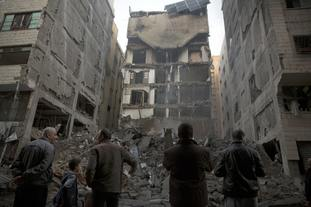 Palestinians check the damage of a destroyed residential building hit by Israeli airstrikes in Gaza City