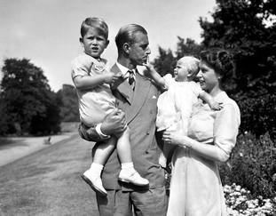 Princess Anne in the arms of Princess Elizabeth, with the Duke of Edinburgh, holding Prince Charles, in the grounds of Clarence House, their London residence in 1951