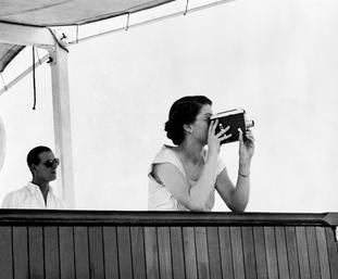 The Queen, with Philip, taking a cine-film of the historic hand-over of escort duty from the cruiser Sheffield, which was returning to Panama, to the New Zealand light cruiser Black Prince in 1953