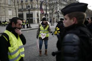 Demonstrators wearing yellow vests talk to police officers on the Champs-Elysees in Paris