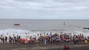 Dozens have taken a New Year's Day dip in the chilly sea at Sheringham, Norfolk.