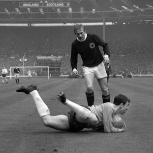 At the feet of Scotland's Denis Law.