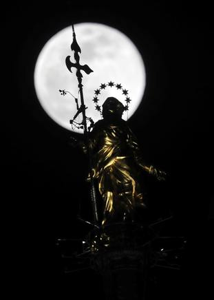 The supermoon rises behind a statue of the Virgin Mary in Milan