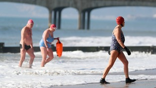 Swimmers enjoy the warm weather at Boscombe beach in Dorset.