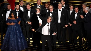Peter Farrelly, center, and the cast and crew of Green Book.