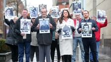Relatives of those killed in the Ballymurphy massacre hold their pictures outside court in Belfast
