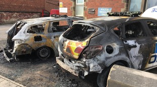 Picture of two police cars after they were set alight.
