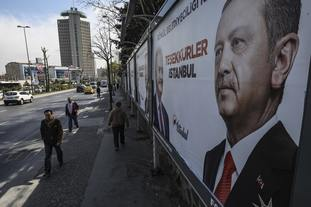 People walk past posters showing Turkey's President Recep Tayyip Erdogan and Binali Yildirim, the mayoral candidate for Istanbul