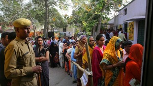 Indians stand in queues to cast their votes at a polling booth for the first phase of general elections