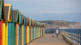 A couple walk alongside colourful beach huts on Whitby beach in Yorkshire.